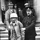 Photograph of the suffragette Fanny Parker, alias Janet Arthur, being escorted from Ayr Sheriff Court by a police officer. Miss Parker, a niece of Lord Kitchener, faced trial for attempting to burn Robert Burn's cottage in Alloway, 1914 (Crown Copyright, National Records of Scotland, HH16/43/58)