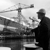 Photograph of three quarter bow view of the Cunard liner RMS Queen Elizabeth 2, with ship worker in foreground, taken from west side of dock during construction at the shipyard of John Brown and Company, Clydebank, 30 Aug 1967 (Crown Copyright, National Records of Scotland, UCS1/118/736/1155)