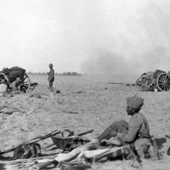 Photograph of a Royal Field Artillery Battery in action with an Indian sepoy in the left foreground in Mesopotamia, circa 1917 (Crown Copyright, National Records of Scotland, GD372/288/11)