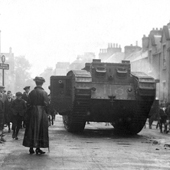 Photograph of a World War I Mark V (Male) Tank in Callander high street with crowds and woman in foreground, circa 1917 (Crown Copyright, National Records of Scotland, NSC1/392/1/8)