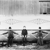 Photograph of two men, who on the left and right of the photograph represent two piers, stick between them represents the central girder, and the young man sitting in the middle represents the load being placed on the central girder, 1887 (Crown Copyright, National Records of Scotland, BR/FOR/4/34/161)