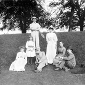 Photograph of a group of three women, a child and three men posed on a small bank. The man on on the right of the group is Forth Bridge designer Benjamin Baker, July 1888 (Crown Copyright, National Records of Scotland, BR/FOR/4/34/68)