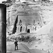 Photograph of the view of the Great Temple at Abu Simbel showing the colossi of Ramesses II taken from the deck of a steam boat, a crowd of people look on as a man standing just fore of the funnel takes a picture, Nile Pleasure Cruise, 1898 (Crown Copyright, National Records of Scotland, GD268/1055/53e)