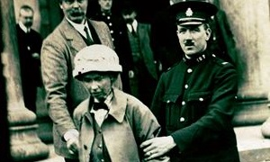 Image of Fanny Parker being escorted from Ayr Sheriff Court accused of attempting to bomb Robert Burns cottage in Alloway.