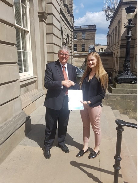 Image- Lindsay Turpie, Records and Information Management Officer for Dumfries and Galloway Council, is pictured handing over the RMP to Hugh Hagan, Senior Public Records Officer of the Assessment Team.