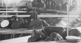 Detail from a glass plate negative of naval ratings asleep at mess tables on HMS Inflexible, presumably during her trials, 1908. The original negative is cracked (UCS1/118/374/39).