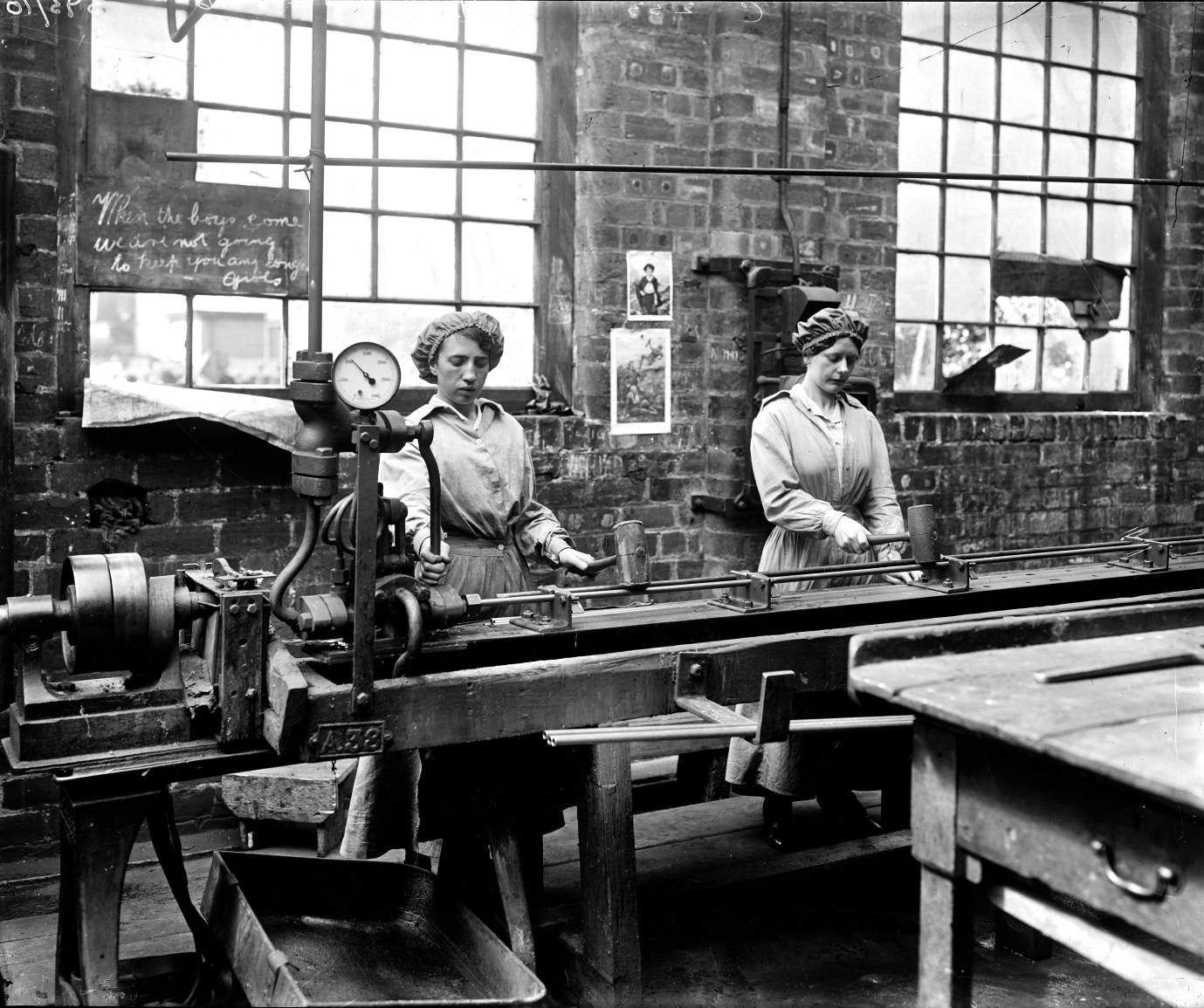 Women workers testing condenser tubes at John Brown & Co's yard at Clydebank. Hostility to women 'dilutees' is evidence in the chalked message, 'When the boys come [back] we are not going to keep you any longer girls', National Records of Scotland (archive reference: UCS1/118/Gen/393/10)